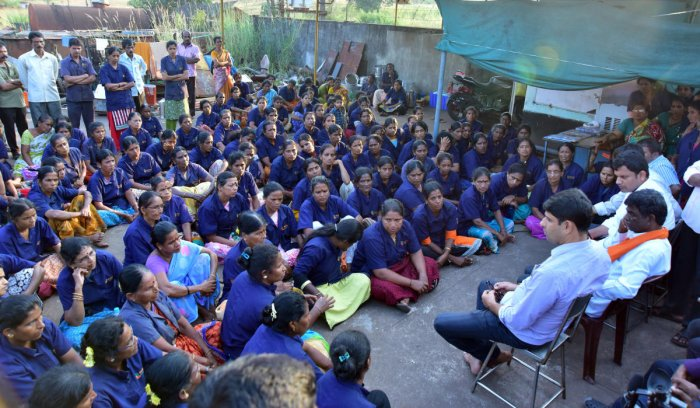 Leader of Opposition in the Legislative Council Kota Srinivas Poojary speaks to protesting labourers outside cashew factory in Shaktinagar on Sunday.