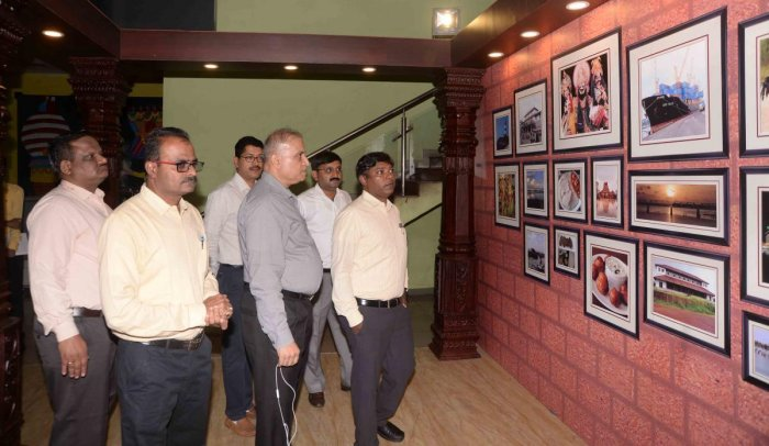Deputy Commissioner Sasikanth Senthil looks at the photographs displayed at the information kiosk, at New Mangalore Port.