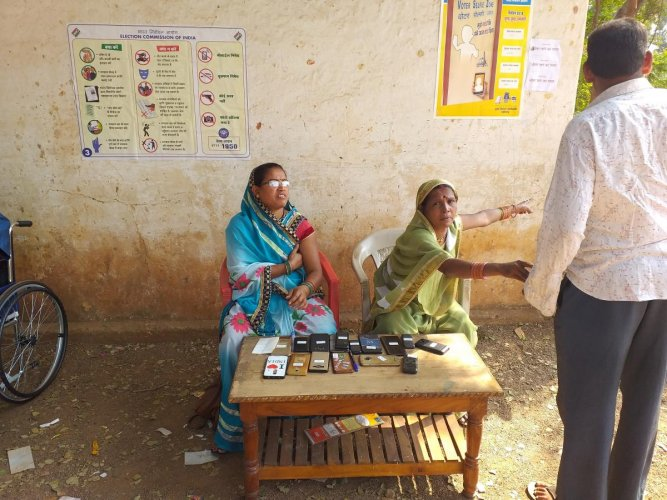 Two women guarding the mobile phones of electors who have gone into the booth to vote, at 47-Dharsiwa in Baroundaon the outer limits of Raipur. DH PHOTO