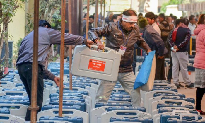 Election officials collect their Electronic Voting Machine (EVM) from an EVM distribution centre in Jabalpur. Congress has charged that BJP was manipulating the EVMs with bluetooths. PTI
