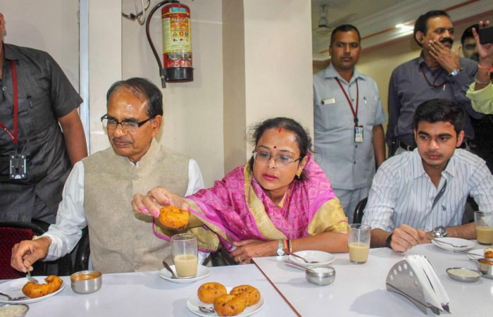 Madhya Pradesh Chief Minister Shivraj Singh Chouhan along with his wife Sadhna Singh and son Kunal Singh Chouhan enjoys snacks during a visit to Indian Coffee House in Bhopal on Tuesday. PTI