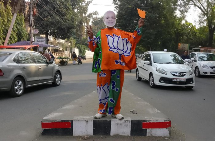 REFILE - REMOVING ERRONEOUS INFORMATION A supporter of India's Bharatiya Janata Party (BJP) wears a mask depicting the Indian Prime Minister Narendra Modi, and drapes himself with flags of BJP's symbol at a traffic signal in Bhopal, India, November 20, 20