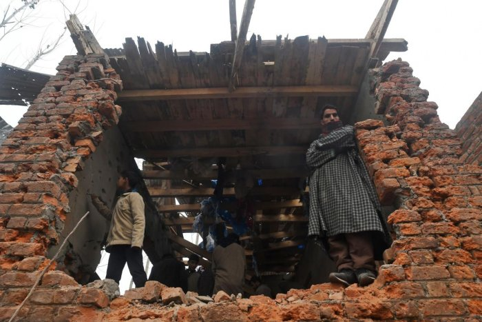 People inspect a damaged house after a gunfight between militants and security forces at Mujgund area on the outskirts of Srinagar. (AFP Photo)