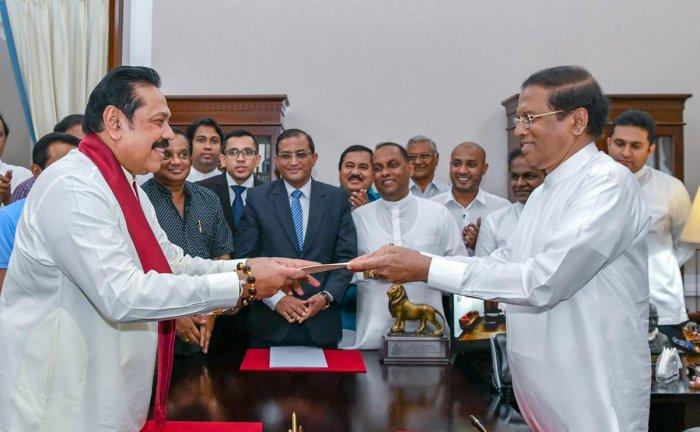 Former Sri Lankan president Mahinda Rajapakse (L) handing over documents to Sri Lankan President Maithripala Sirisena (R) as Rajapakse is sworn in as new Prime Minister, in Colombo. (Photo by Handout / Sri Lanka President Media / AFP)