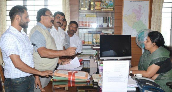Congress leader Arun Machaiah speaks to Deputy Commissioner P I Sreevidya, in Madikeri on Tuesday.