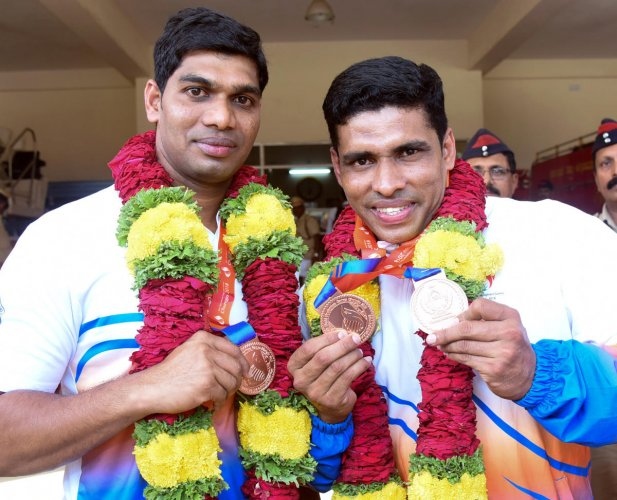 Rajesh K Madival and Ashwin Sanil from the Fire Fighting and Emergency Services Department display their medals won at the 13th International sports event meant for fire fighting and emergency staff at Chungyu in South Korea.