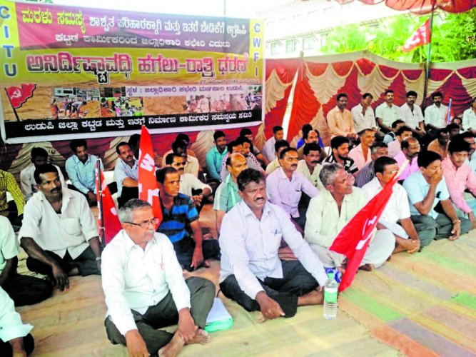 Udupi District Building and Other Construction Workers' Coordination Committee members stage a stir in front of the DC's office in Manipal on Tuesday.
