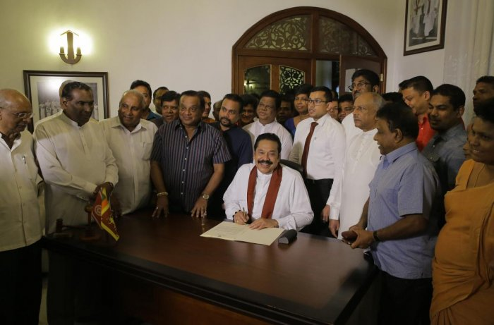 Sri Lanka's disputed Prime Minister Mahinda Rajapaksa signs his resignation letter at his residence in Colombo, Sri Lanka, Saturday. AP/PTI photo