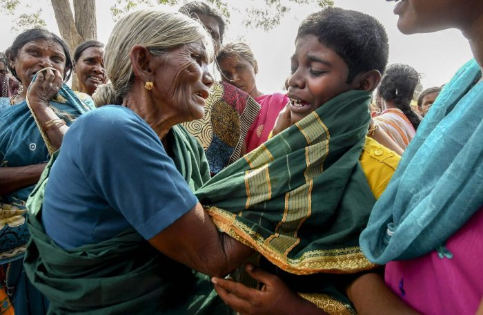 A crying boy being consoled by his grandmother after his mother died of suspected food poisoning at Bidarahalli, near Sulawadi village in Chamarajnagar district of Karnataka. PTI photo