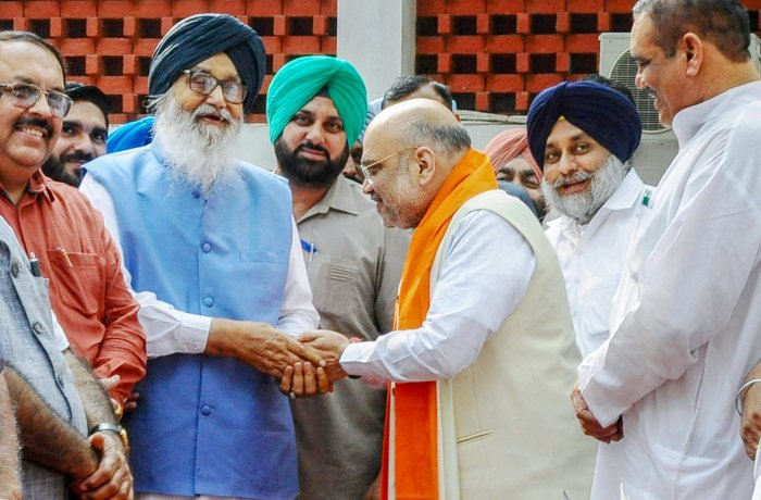 BJP president Amit Shah greets former Punjab chief minister Parkash Singh Badal as Sukhbir Singh Badal looks on, in Chandigarh on Thursday. PTI