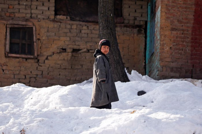 A boy stands on snow outside his home on a cold winter morning at Haripora Village, South Kashmir. REUTERS
