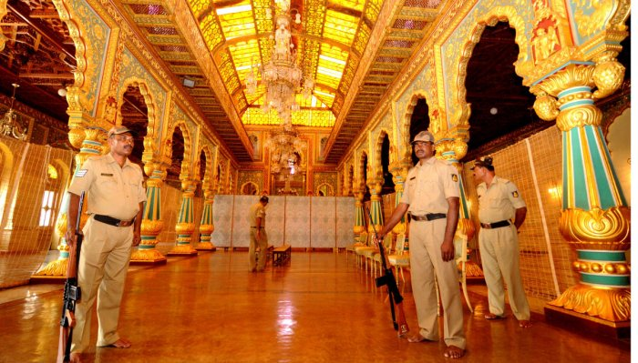 Police personnel guard the assembled Simhasana at the Durbar Hall of the Mysuru Palace, in Mysuru, on Thursday.