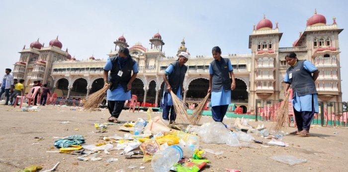 Civic workers clean Mysuru Palace premises, where thousands of people gathered to witness Dasara Jamboo Savari, on Saturday.