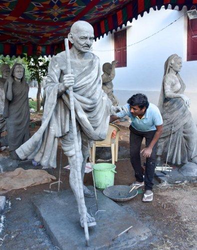 An artist works on a cement sculpture of Mahatma Gandhi during the camp organised as part of Gandhi's 150th birth anniversary at Gandhi Bhavan, University of Mysore, in Mysuru, on Saturday.