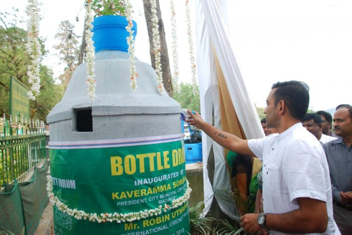 Cricketer Robin Uthappa inaugurates the bottle dropper as part of the World Heritage Day and World Toilet Day programme at Raja Seat in Madikeri on Monday.