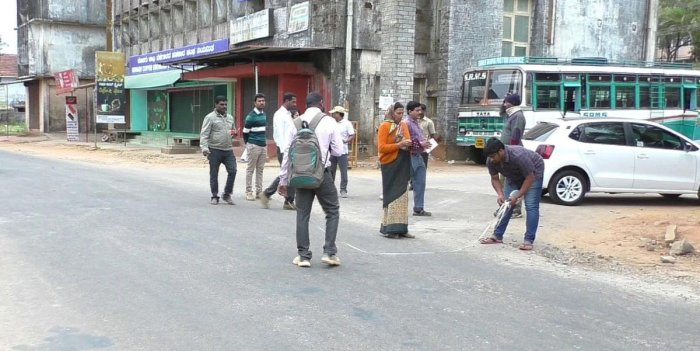 Marking work being carried out for the widening of Raja Seat Road, in Madikeri, on Friday.