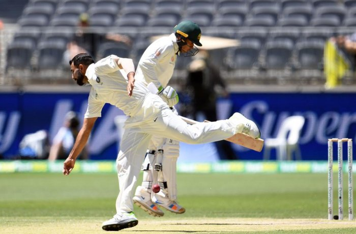 India's bowler Mohammed Shami (L) attempts to field the ball as Australia's batsman Usman Khawaja runs back to the crease during day four of the second Test cricket match between Australia and India in Perth. AFP Photo