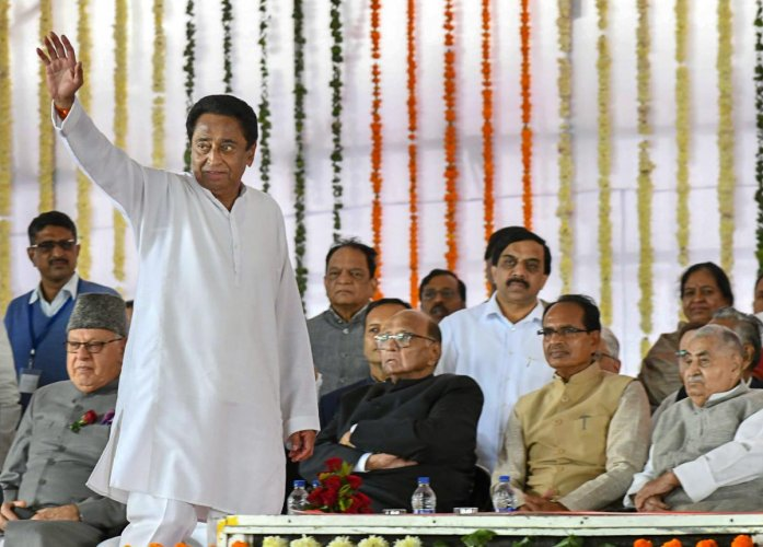 Newly-sworn in Madhya Pradesh Chief Minister Kamal Nath waves at the crowd during his swearing-in-ceremony, in Bhopal, Monday, Dec. 17, 2018. Also seen are NC chief Farooq Abdullah (L), NCP chief Sharad Pawar, former MP CM Shivraj Singh Chouhan and others