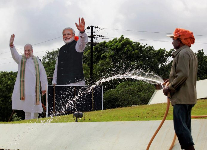 A worker sprinkles water with the cutouts of Prime Minister Narendra Modi and BJP president Amit Shah in the backdrop, ahead of BJP's public meeting, in Bhubaneswar, on Friday. PTI