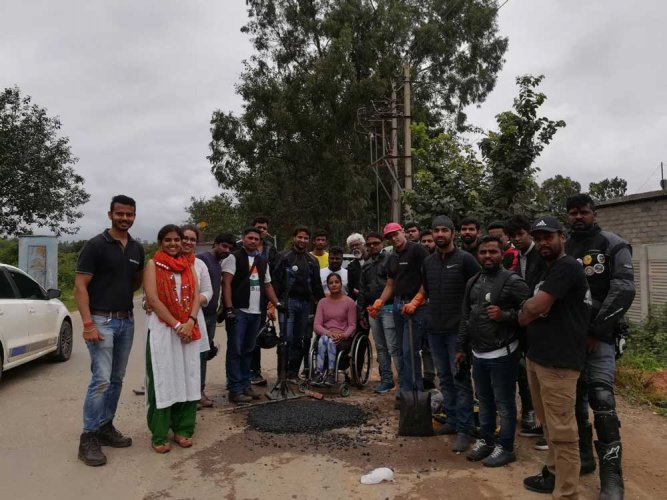 Residents of Whitefiled fix a pothole in their area. Special arrangement
