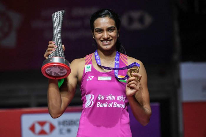 P V Sindhu poses with her trophy after the women's singles final match at the 2018 BWF World Tour Finals badminton competition in Guangzhou, China. AFP
