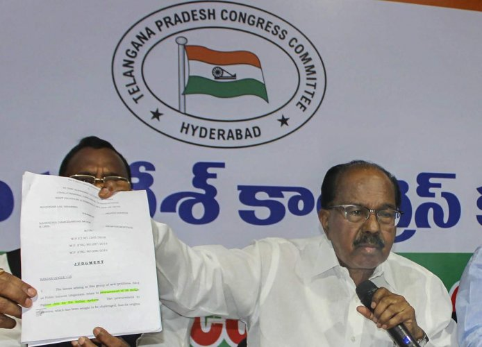 Parliamentary Standing Committee Chairman Veerappa Moily shows Supreme Court's order copy regarding Rafale Deal during a press conference, in Hyderabad. (PTI Photo)