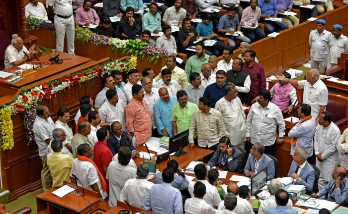 BJP leaders stage a protest in the Assembly in Belagavi on Thursday demanding farm loan waiver. DH photo/M S Manjunath