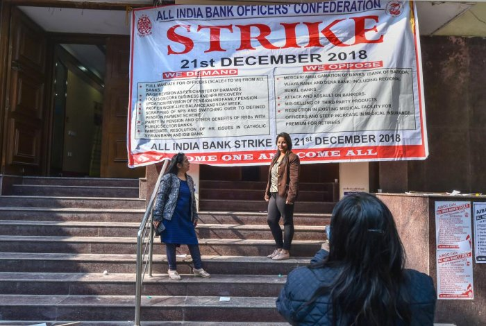 Bank employees click photos outside a closed bank office during a nationwide strike called by All India Bank Officers' Confederation (AIBOC), in New Delhi, Friday (PTI Photo)