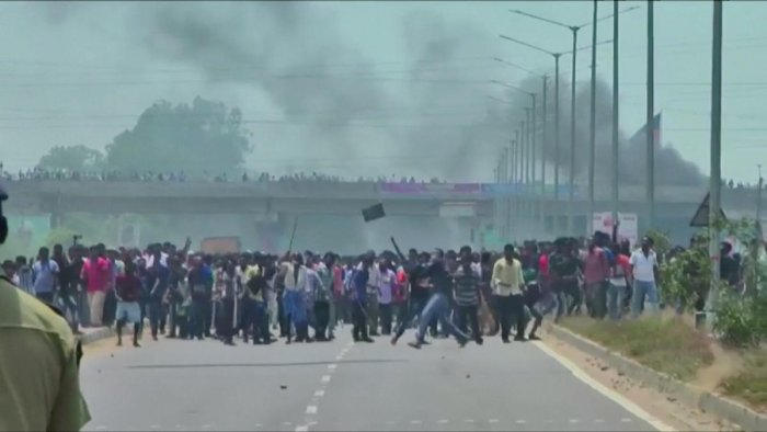 People pelt stones during a protest against the construction of a copper smelter by Vedanta Resources from the road, in Thoothukudi, Tamil Nadu, India in this still image from May 22, 2018 video footage. Video taken May 22, 2018. (ANI via REUTERS)