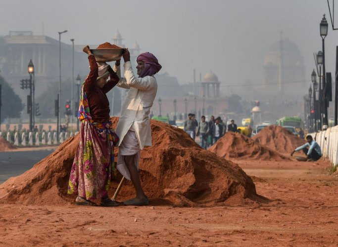Workers level the footpath to prepare Rajpath for the upcoming Republic Day function, in New Delhi, Saturday. (PTI Photo)