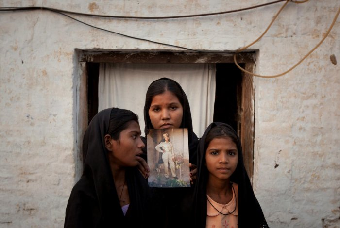 The daughters of Pakistani Christian woman Asia Bibi pose with an image of their mother while standing outside their residence in Sheikhupura located in Pakistan's Punjab Province. (Reuters File Photo)