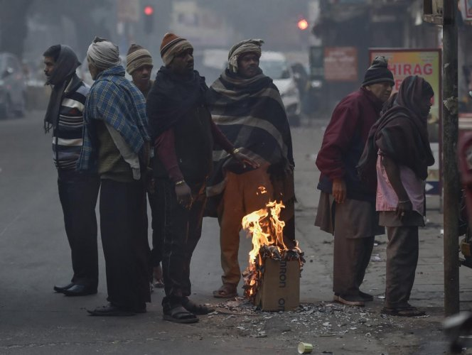 People gather around a makeshift bonfire to warm themselves on a cold, foggy morning, in New Delhi, on Sunday. PTI