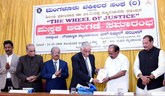 Supreme Court judge Justice S Abdul Nazeer releases former Union minister Veerappa Moily's book 'The Wheel of Justice' at the district court complex in Mangaluru on Monday.