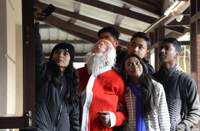 Youths take a selfie with a Santa Claus figure during a Christmas Day service at a Catholic church in Srinagar on Tuesday. AFP