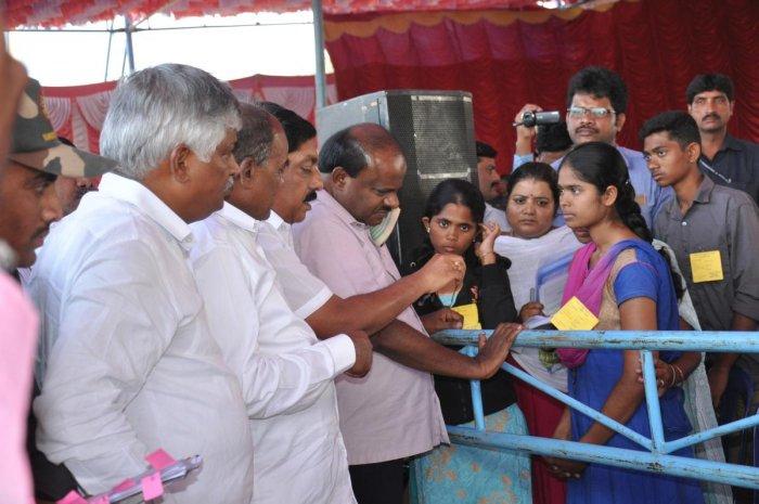 Chief Minister H D Kumaraswamy interacts with the daughters of prasdam victims Mylibai and Krishnanayaka, during his visit to Sulvadi village, Hanur taluk, Chamarajanagar district, on Tuesday.