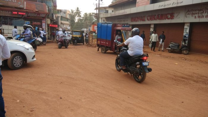 Vehicle users and pedestrians struggle to pass through Nellikayi Road-Mission Street Junction in Mangaluru, where the road is not yet asphalted.