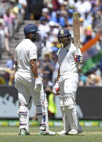 COMPOSED KNOCK: India's Mayank Agarwal (right) celebrates his half-century with team-mate Cheteshwar Pujara on the first day of the third Test at the Melbourne Cricket Ground in Melbourne on Wednesday. AP/PTI