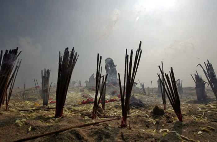 Incense sticks burn as a girl prays during a prayer ceremony for the victims of the 2004 tsunami on the 14th anniversary of the disaster, at Marina beach in Chennai. (Reuters Photo)