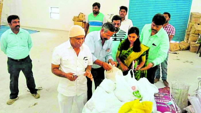 MLA Appacchu Ranjan pays a visit to the APMC warehouse in Kushalnagar on Wednesday and inspects the quality of the leftover relief materials.