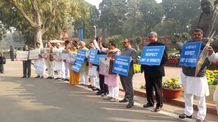 MPs from Karnataka stage protest in front of Mahatma Gandhi statue in the Parliament complex demanding early implementation of Mekedatu project on Thursday. (DH Photo)