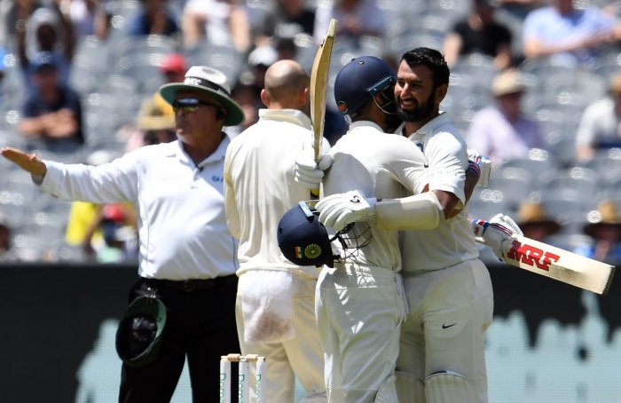 India batsman Cheteshwar Pujara (R) celebrates his century with teammate Virat Kohli on day two of the third Test against Australia in Melbourne on December 27, 2018. (AFP Photo)