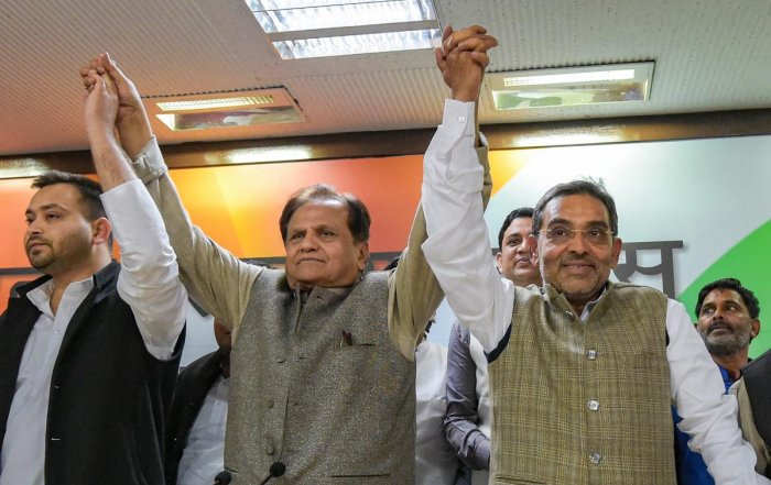 Rashtriya Lok Samta Party (RLSP) leader Upendra Kushwaha (R) raises hands with others Congress party's Ahmed Patel and RJD's Tejashwi Yadav after joining the grand alliance during a press conference at AICC in New Delhi. (PTI Photo)