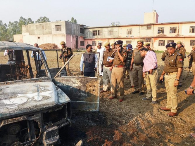 Policemen inspect after several vehicles were set on fire by a mob during a protest over the alleged illegal slaughter of cattle, in Bulandshahr, Monday, Dec. 03, 2018. According to Additional Director General of Meerut zone Prashant Kumar, protesters fro