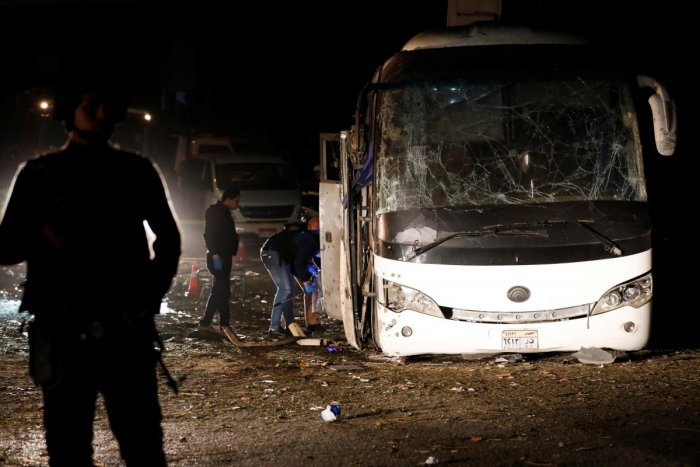 Police officers inspect a scene of a bus blast in Giza, Egypt, on Friday. (REUTERS)
