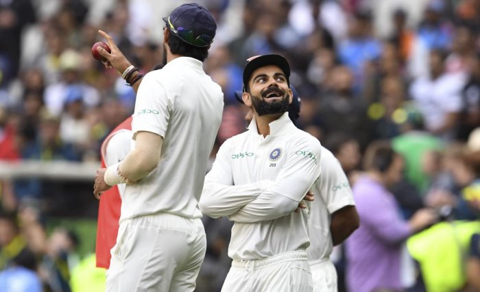 India's captain Virat Kohli (R) and teammate Ishant Sharma (L) watch the rain come down on the final day of the third cricket Test match between Australia and India in Melbourne on December 30, 2018. (Photo by WILLIAM WEST / AFP)