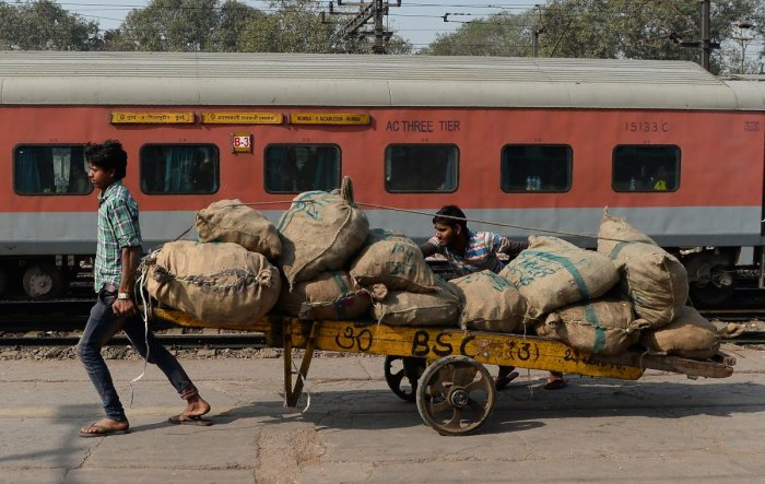 TOPSHOT - Indian labourers transport goods loaded on a handcart at a railway station in New Delhi on February 1, 2018. / AFP PHOTO / SAJJAD HUSSAIN