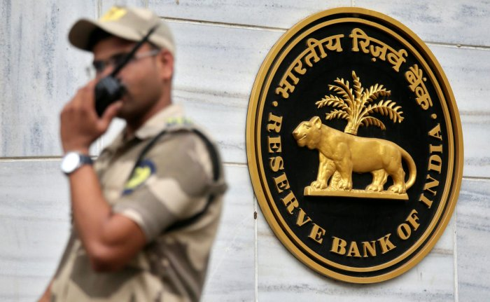 FILE PHOTO: A guard stands next to the Reserve Bank of India (RBI) logo outside its headquarters in Mumbai, India, October 5, 2018. REUTERS/Francis Mascarenhas/File Photo