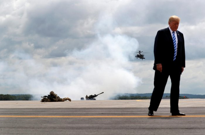 """U.S. President Donald Trump observes a demonstration with U.S. Army 10th Mountain Division troops, an attack helicopter and artillery as he visits Fort Drum, New York, U.S., August 13, 2018. Reuters photographer Carlos Barria: """"President Trump often talks"""