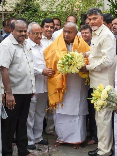Andhra Pradesh Chief Minister N Chandrababu Naidu (R) presents a bouquet to former prime minister HD Devegowda as Karnataka Chief Minister HD Kumaraswamy (L) looks on, before a meeting in Bengaluru on Thursday. PTI