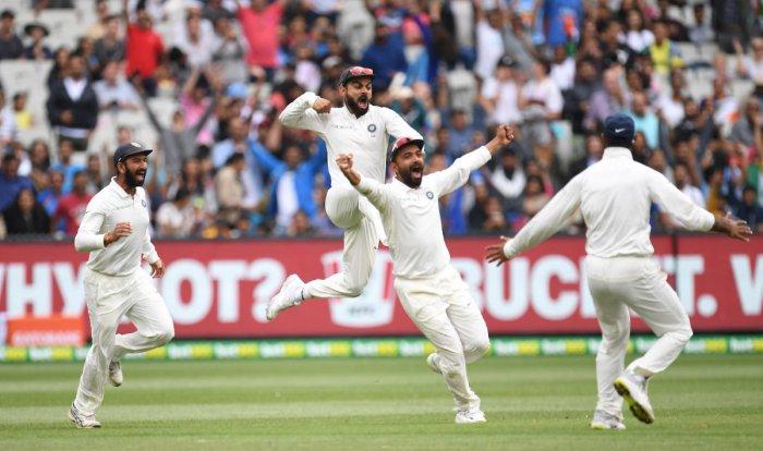 Thunder down under: Virat Kohli (2nd L) celebrates with Cheteshwar Pujara and Ajinkya Rahane after winning the third test match against Australia at the MCG in Melbourne. Reuters